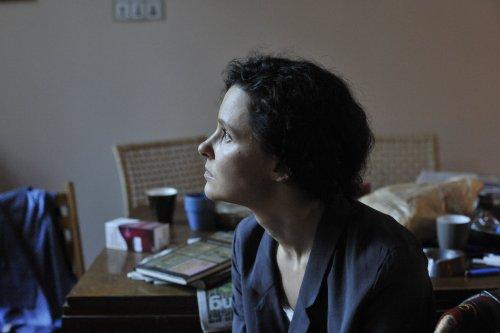 Een vrouw met donker haar staart ernstig voor zich uit.