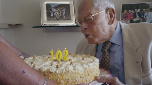 Een man met wit haar blaast kaarsjes in de vorm van het getal 102 uit op een verjaardagstaart.