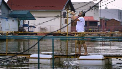 Een man met kort grijs haar en een baard staat op een drijvend bruggetje en speelt trompet.