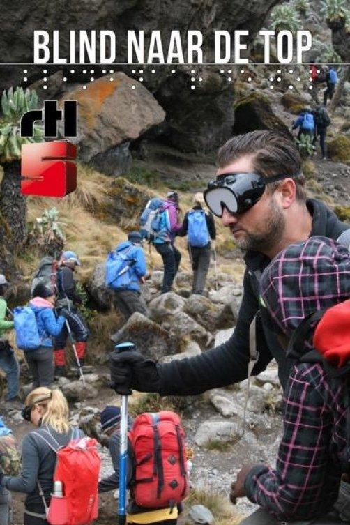 Blind naar de top, RTL5. Een groep mensen beklimt een berg. De man op de voorgrond is geblinddoekt.