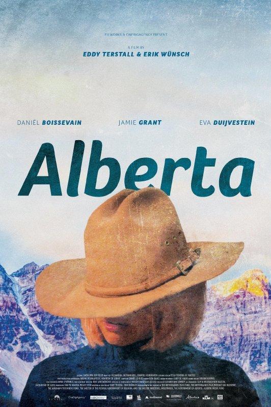 Alberta. Onder een grote cowboyhoed schuilt het gezicht van een blonde vrouw. Op de achtergrond hoge besneeuwde bergtoppen.