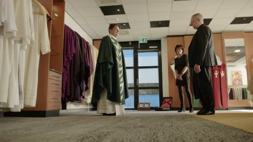 Bert Glorie past een groen priestergewaad aan. Priester Nico Krol kijkt kritisch. Een vrouw staat er glimlachend bij.