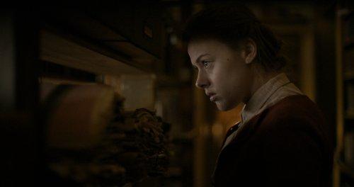 Een blonde, jonge vrouw kijkt vanuit een donkere ruimte door een raampje naar buiten.