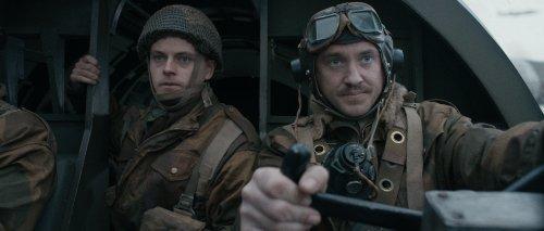 Een piloot en militair kijken gespannen vooruit in de cockpit van een gevechtsvliegtuig.