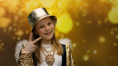 Rudy steekt twee vingers op en kijkt lachend voor zich uit. Hij draagt een gouden jas, hoed en glimmende kettingen.