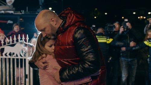 Rudy's vader en zus omhelzen elkaar in het donker op straat. Politiemannen houden het publiek en fotografen op afstand.