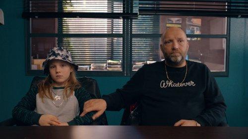 Rudy zit naast zijn vader, die een hand op zijn arm legt. Ze zitten in een sobere kamer achter een bureau.