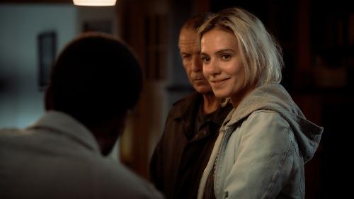 Puk lacht naar een man. Luther staat met een strak gezicht achter haar.