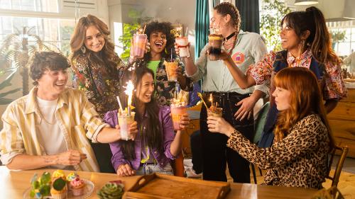 Een groep jonge mensen proost met vrolijk versierde drankjes in een woonkamer.