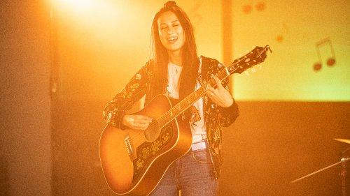 Een meisje met lang donker haar staat in een geel verlichte ruimte en speelt gitaar en zingt.