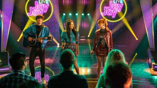 Julia, Nick en Sterra staan op een podium. Nick speelt gitaar en de meisjes hebben een microfoon vast.