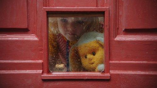 Dropje en een blond meisje kijken door een raampje in een deur naar buiten.