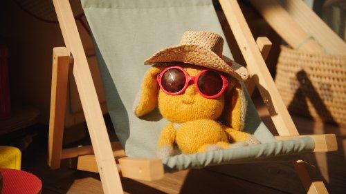 Dropje ligt met een zonnebril en een hoed op in een strandstoeltje.