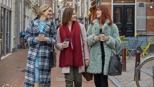 Drie jonge vrouwen lopen met een koffiebeker in hun hand door de stad.