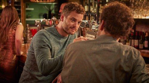 Twee jonge mannen voeren een gesprek aan de bar.