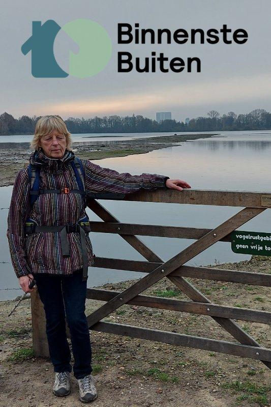BinnensteBuiten. Anneke Berkhout staat tegen een hek geleund in een natuurgebied. Ze heeft een rugzak om en een taststok vast.