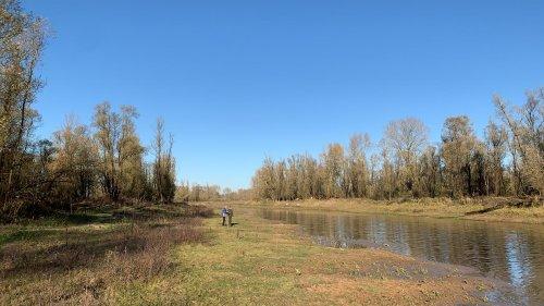 Twee mensen staan in een natuurgebied naast een kanaal. Het is zonnig en de blauwe lucht reflecteert in het water.