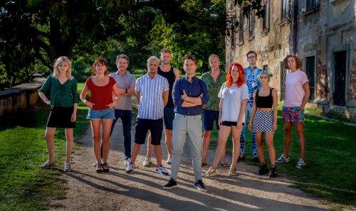 Rik van de Westelaken staat met de kandidaten van seizoen 21 van Wie is de Mol? in een groene omgeving naast een groot gebouw.