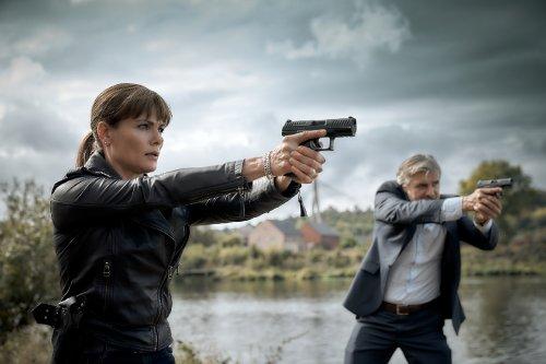 Eva van Dongen en Floris Wolfs staan met getrokken pistolen aan de rand van een rivier.