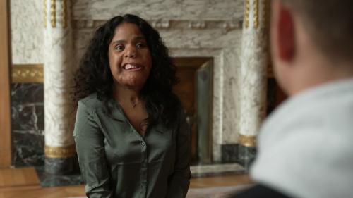 Een vrouw met donker haar en een deformatie in haar gezicht praat met Jurre Geluk.