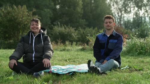 Jurre Geluk en een jonge vrouw met kort haar zitten met hun ogen dicht op een grasveld.