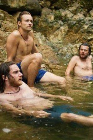 Off track. Drie jonge mannen elk ik een blauwe zwembroek zitten tegen een rotswand in het water.