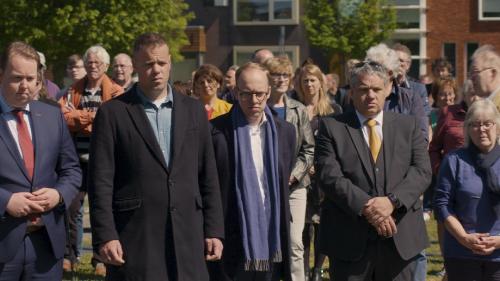 Een groep mensen met nette kleding en serieuze gezichten staan op een open plek in een woonwijk bij elkaar.