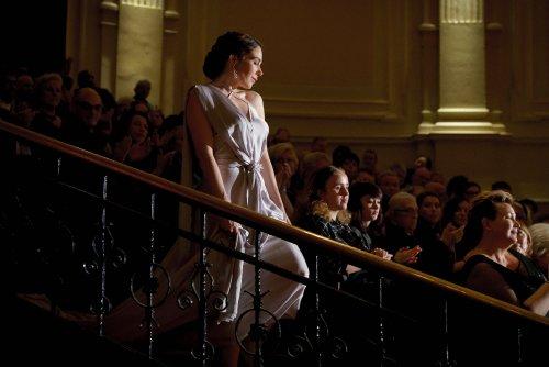 Een mooi opgemaakte vrouw in een lange, zijden jurk met sleep loopt de trap af in een volle concertzaal terwijl het publiek klapt.