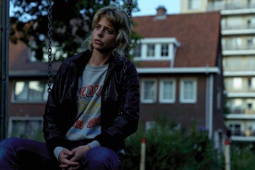 Een blonde vrouw met een spijkerbroek en een zwart jack aan zit op een schommel in een woonwijk. Ze kijkt nadenkend voor zich uit.