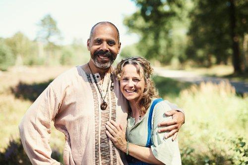 Een man en een vrouw met hippiekleren aan staan lachend en gearmd naast elkaar in een grasveld.