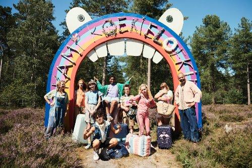 De kinderen en leiding van Kamp Koekieloekie staan buiten onder een vrolijk versierde boog.