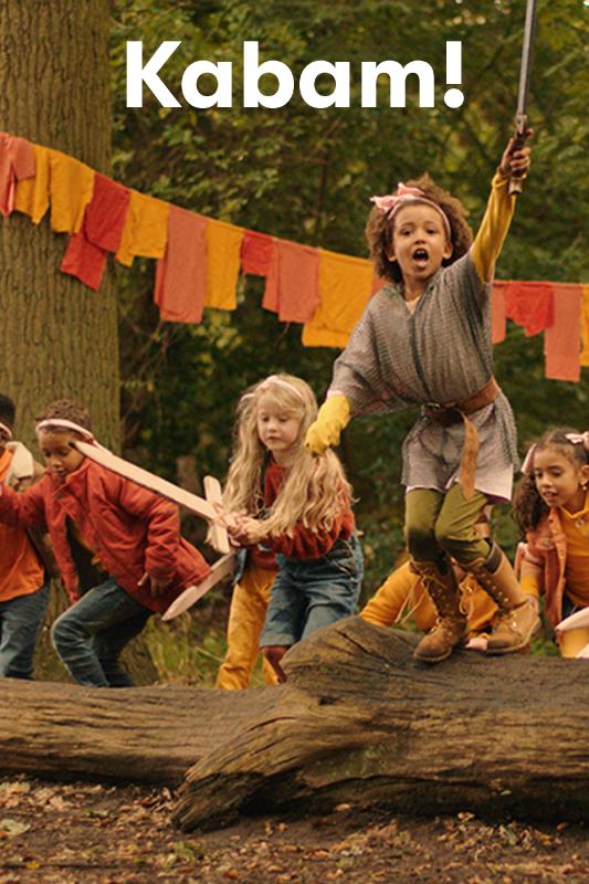 Kabam! Kinderen met nepzwaarden in hun handen springen over een boomstam in het bos.