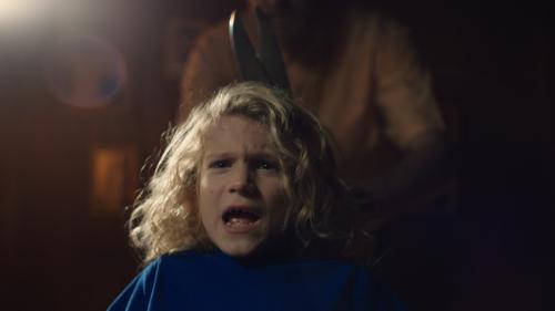 Een kindje met lange blonde krullen schreeuwt het uit van angst. Achter hem staat een persoon met een hele grote schaar.