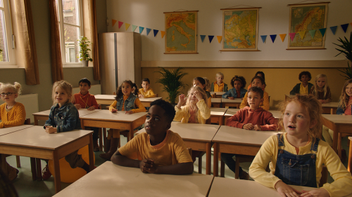 Een groep kinderen zit in een klaslokaal.