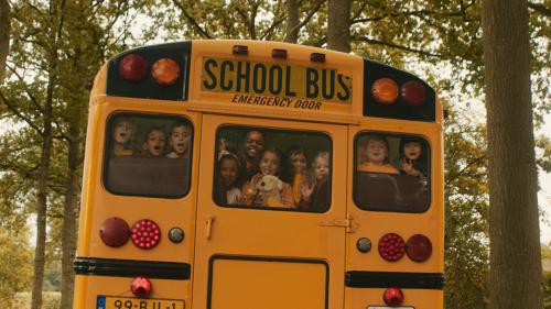 Een stuk of tien kinderen kijken uit de achterruit van ene gele schoolbus.