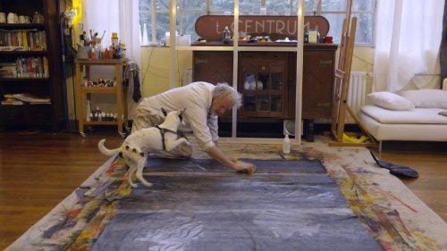 Een man met grijs haar zit op de grond in een woonkamer aan een groot schilderij te werken. Naast hem springt een wit hondje enthousiast omhoog.