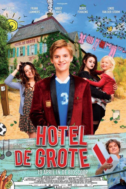 Hotel de grote L. Een blonde jongen in een rode colbert lacht. Achter hem twee tienermeisjes en een klein blond meisje. Ze staan allemaal voor Hotel de grote L.