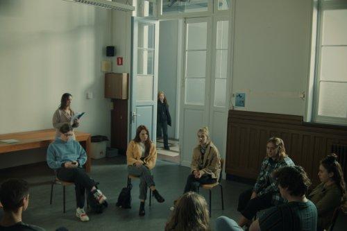 Een groep jongeren zit in een kring in een klaslokaal. Achter hen staat een vrouw tegen een tafel geleund met een map in haar handen.