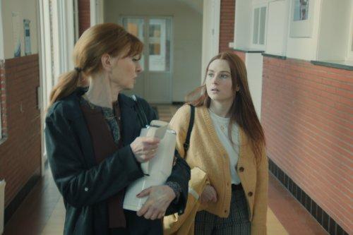 Hanne en haar moeder lopen door een gang op school. Ze hebben allebei rood haar.