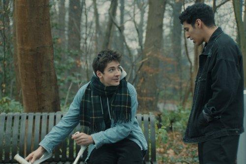 Tom zit buiten op een bankje en kijkt op naar Yassin, die tegen hem praat.