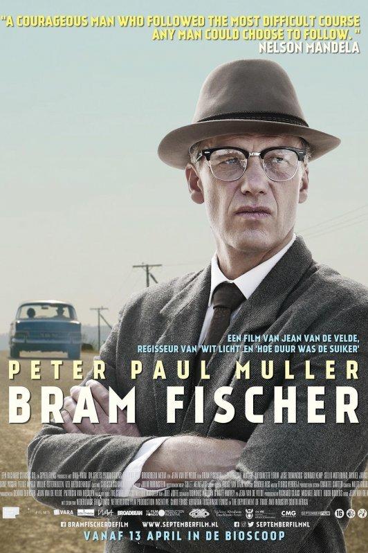 Bram Fischer. Een man in pak met hoed en bril staat met zijn armen over elkaar bij een weg. In de verte rijdt een auto langs elektriciteitspalen.