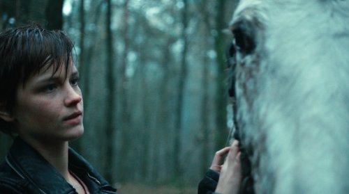 Een meisje met kort haar staat buiten naast een paard.