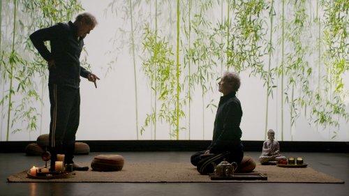 Een Marcel Hensema rechts zit met een open blik op een yogakussen terwijl een Marcel Hensema links tegenover hem staan en sceptisch naar het kussen aan zijn voeten wijst.