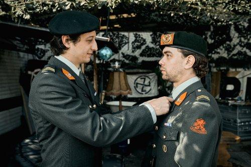Een militair doet de stropdas van een andere militair recht.