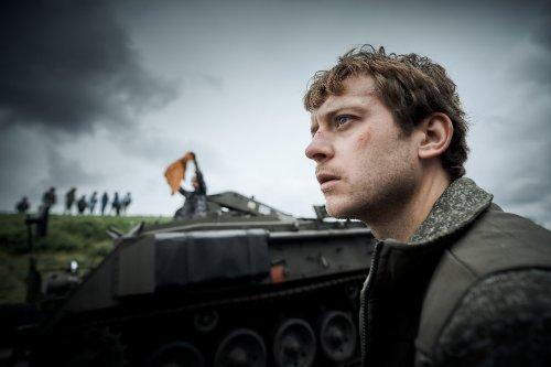 Een man met een schram op zijn wang kijkt serieus voor zich uit. Achter hem rijdt een tank met daarop iemand die een oranje vlag omhoog houdt.