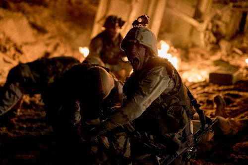Een militair schreeuwt op een slagveld in het donker.