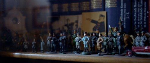 Een leger aan beeldjes van fascisten staat op een plank uitgestald.