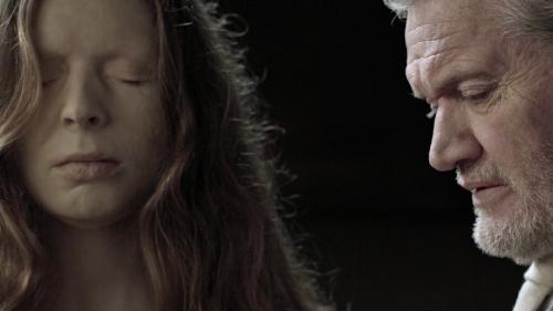 Een jonge vrouw met lang haar heeft haar ogen gesloten en trekt een gepijnigd gezicht. Een oudere man met grijs haar kijkt met neergeslagen ogen naar beneden.