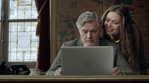 Een man met grijs haar kijkt geconcentreerd naar het scherm van een laptop. Een jonge vrouw met lang haar staat vlak achter hem en kijkt lachend mee over zijn schouder.