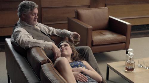 Een man met grijs haar zit op een leren bank. Hij kijkt naar de jonge vrouw die met haar hoofd op zijn been naast hem ligt.